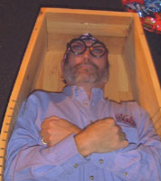A mock burial of a modern man with his arms crossed reminiscent of ancient burials.